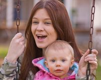 Young Mother and Baby Daughter on Swings. Young mother is laughing while swinging with baby daughter in a family moment of fun Royalty Free Stock Photo