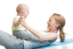 Young mother and baby are doing exercise and having fun on a white background. Young mother and baby are doing exercise and having fun  on a white background Stock Photo