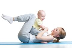 Young mother and baby are doing exercise and having fun on a white background. Young mother and baby are doing exercise and having fun isolated on a white Royalty Free Stock Photos