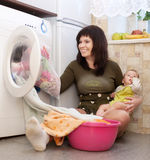 Young mother with baby doing laundry Royalty Free Stock Photo
