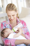 Young Mother With Baby Feeding On Sofa At Home Stock Image