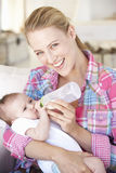 Young Mother With Baby Feeding On Sofa At Home Royalty Free Stock Images