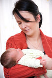 Young mother with baby girl. Portrait of young mother cradling cute baby girl indoors Royalty Free Stock Photos