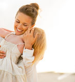 Young mother and baby girl hugging on beach Royalty Free Stock Photography