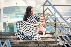 Young mother and baby girl sitting on stairs on street Stock Photo