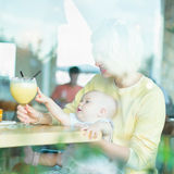 Young mother with baby having some drink in cafe. Baby girl pointing glass of mango smoothie stock photos