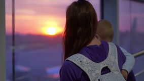 A mother with a baby in her arms looks out the window at the planes, slow motion. Young mother with a baby in her arms looks out the window at the planes in the stock footage