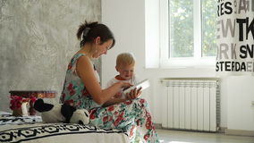 Young mother with a baby look at the tablet and smiles in the room with sun light. stock video footage