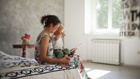 Young mother with a baby look at the tablet and smiles in the room with sun light. stock footage