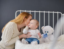 Young mother and baby lying on the bed playing with a bear toy Royalty Free Stock Photo