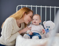 Young mother and baby lying on the bed playing with a bear toy Stock Photo