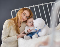 Young mother and baby lying on the bed playing with a bear toy Stock Image