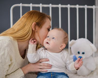 Young mother and baby lying on the bed playing with a bear toy Stock Images