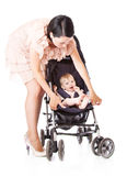 Young mother with baby in perambulator royalty free stock photo