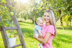 Young mother with baby picking apples from an apple tree Royalty Free Stock Photos