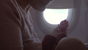 Air travel with baby daughter. Young mother and baby in plane. Woman playing with child and kissing beloved daughter. Family travel by plane stock video