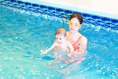Young mother and baby playing in swimming pool. Young mother and her little baby playing in a swimming pool royalty free stock photography