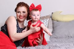 Young mother and baby in red dress on bed. With pillows in bedroom Stock Photography