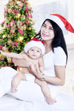 Young mother with baby with santa hats Stock Photos