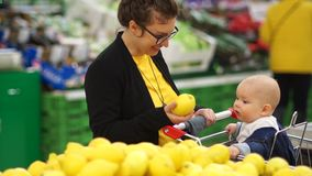 Young mother with baby shopping in supermarket. The child looks at lemon with delight, the development of kids