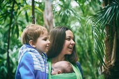 A young mother with a baby in a sling and little boy is walking in the jungle. A young mother with a baby in a sling and little boy is walking in the tropical Royalty Free Stock Photos