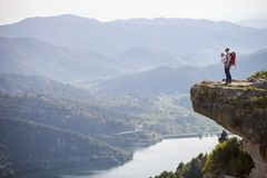 Young mother with baby in sling standing on cliff Royalty Free Stock Photography