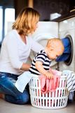 Young mother with a baby boy doing housework. Young mother with a baby son doing housework. Beautiful women and baby boy doing laundry. Baby boy in the laundry Royalty Free Stock Photo
