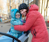 Young mother with baby in stroller Stock Images