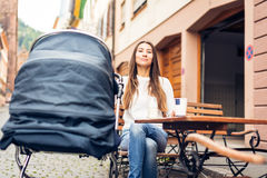 Young Mother With Baby Stroller Having Coffee At A Cafe Royalty Free Stock Photo