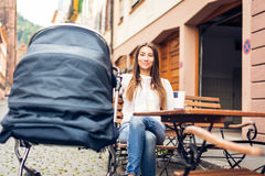 Young Mother With Baby Stroller Having Coffee At A Cafe. In Heidelberg, Germany royalty free stock photography