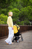 Young mother with baby in stroller outdoors Stock Images