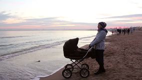 Young mother with a baby on a walk by the sea in the evening. stock video footage