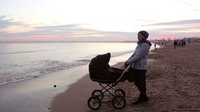 Young mother with a baby on a walk by the sea in the evening. stock footage