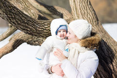 Young mother with baby walking in snowy park Royalty Free Stock Photo
