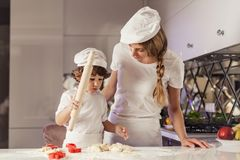 Young mother baking together with her little son in the modern white kitchen. Young mother baking together with her little son in the modern white kitchen Stock Photo