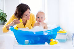 Young mother bathing baby boy Stock Photos