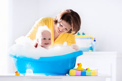 Young mother bathing baby boy Stock Image