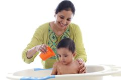 Young mother bathing cheerful baby with foam. Close up royalty free stock photography