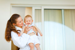 Young mother in bathrobe with happy baby in hand Royalty Free Stock Photo
