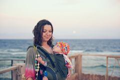 A young mother is on the beach with her baby in a sling Royalty Free Stock Photo