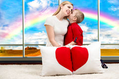 A young mother with a beautiful baby son holding a pillow in shape of heart on the background of the panoramic Windows with a rain. Cushion in heart shape stock photo