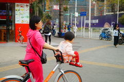 Young mother with a bicycle basket carrying the little girl in the street Royalty Free Stock Photos