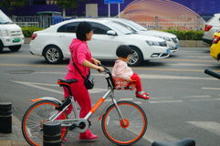 Young mother with a bicycle basket carrying the little girl in the street Royalty Free Stock Photo