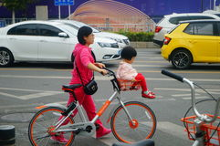 Young mother with a bicycle basket carrying the little girl in the street Royalty Free Stock Images