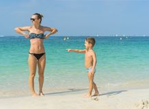 Young mother in black sunglasses and smiling baby boy son playing in the sea in the day time. Positive human emotions, feelings, j. Oy. Splash. Spring and summer Stock Image