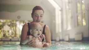 Young mother in black swimming bra preparing her little baby for the first diving into the water, then pull him under. The water for free dive. Slow motion stock video footage