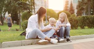 Young mother with blond boy and girl having fun in the summer park.
