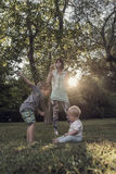 Young mother blowing soap bubbles towards  her two kids Royalty Free Stock Images