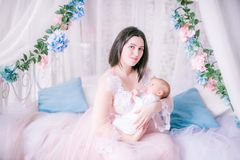 Young mother in a boudoir dress with a baby in her arms by the canopy bed stock photography