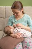 Young mother breast feeding her baby at home Stock Photos